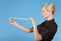 Businesswoman shooting rubber band on blue background