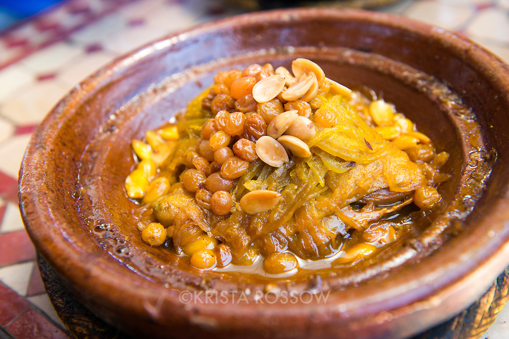 A close-up of a traditional Moroccan chicken tagine dish with peanuts and lemon in a restaurant in Marrakesh, Morocco, near the Medina.