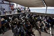 Italy: MSF Dignity1: African migrants sit down on the main deck of the Dignity1 on August 23, 2015. Alessio Romenzi