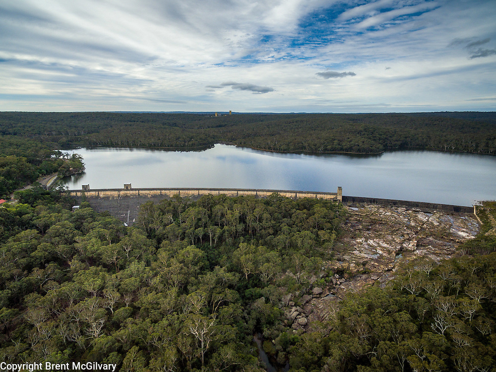 Cordeaux Dam is a curved dam with an unlined side spillway on the left abutment. It is 191 feet (58 m) high, 1,327 feet (404 m) long and holds 93,640 ML (2.060&times;1010 imp gal; 2.474&times;1010 US gal). Construction began in 1918 and was completed in 1926.<br /> The wall consists of large sandstone blocks, quarried onsite and cemented together, faced with a combination of bluestone and sandstone concrete. The blue metal used in the construction of the dam was supplied from the Government Quarries at Kiama and brought by rail to Douglas Park. From here it was conveyed by aerial ropeway across the Nepean Gorge to an interchange on the eastern side where the material was transferred to a 2 ft (610 mm) gauge steam tramway to a point adjacent to the dam site.<br /> By 1867, Sydney was outgrowing the water supply available from Botany Swamps and the Governor (Sir John Young) appointed a Commission to recommend a future water supply. In 1869, the Commission recommended the Upper Nepean Scheme. This comprised weirs on the Cataract and Nepean rivers, a storage reservoir at Prospect and 63.25 miles (101.79 km) of pipelines, tunnels, canals and aqueducts to bring water from the 347 square miles (900 km2) catchment area to Sydney. Work on the Scheme began in 1880 and was completed in 1888. The Scheme was a significant feat of engineering at the time of construction.<br /> As originally built, the Upper Nepean Scheme was capable of supporting an estimated population of 540,000. By 1902, Sydney had a population of 523,000 and was again in the grip of a severe drought. A Royal Commission appointed to report on Sydney's water supply recommended a dam on the Cataract River and construction commenced in the same year. Dams were subsequently built on each of the Cordeaux, Avon and Nepean rivers, with the last being completed in 1935. Each dam includes a public picnic area. In total, the four dams hold 483,600 ML (1.064&times;1011 imp gal; 1.278&times;1011 US gal) and can safely pro