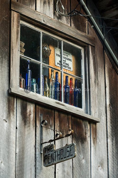 Colorful bottles in a rustic window in Petersburg, Alaska.
