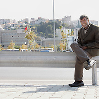 A man sits on a guard railing along a road in Izmir, Turkey
