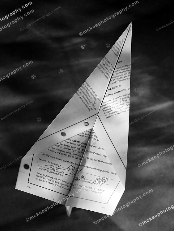 Black and white Paper airplane, made from a patient's medical form.
