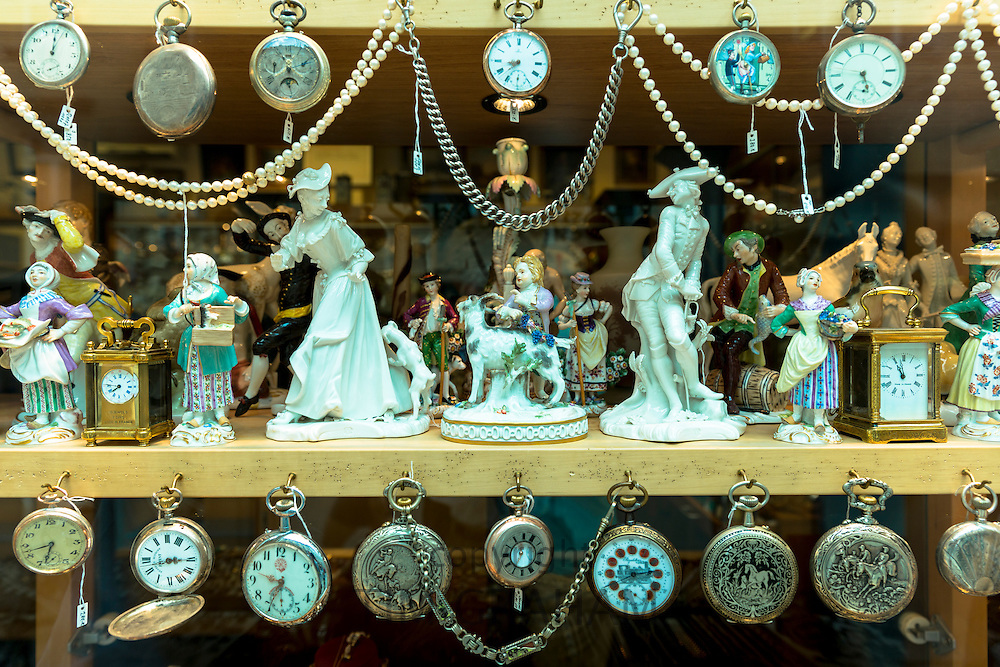 Porcelain figures, clocks and pocket watches on display at Bordhin antique shop in Burgstrasse in Munich, Bavaria, Germany