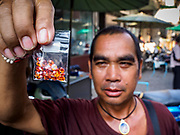 21 DECEMBER 2018 - CHANTABURI, THAILAND: A Thai gem merchant holds up a bag of stones in the gem market in Chantaburi. The gem market in Chantaburi, a provincial town in eastern Thailand, is open on weekends. Chantaburi used to be an active gem mining area in Thailand, but the mines are played out now. Now buyers and sellers come from around the world to Chantaburi for the weekend market. Many of the stones come from Myanmar, others come from mines in Afghanistan and Africa.       PHOTO BY JACK KURTZ