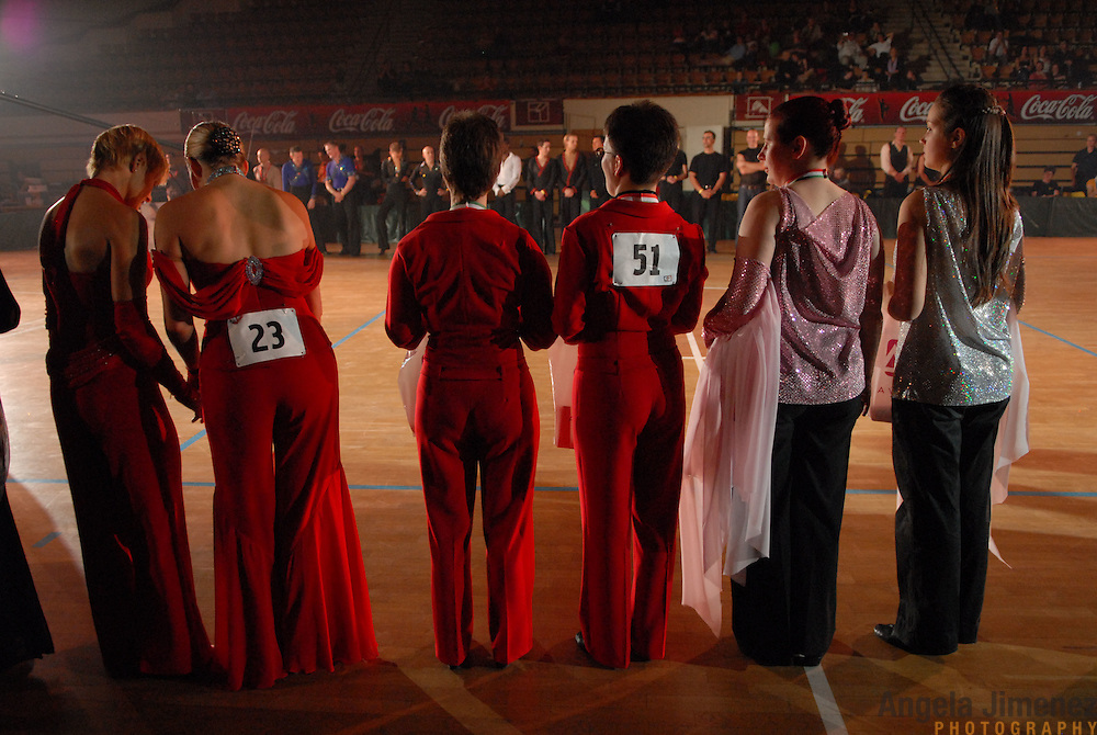 """Same-sex ballroom dance couples line up for the results of the 1st Csardas Cup 2006, the first same-sex international championship ever held in Eastern Europe (which was held prior to the 2nd annual World Championship Same Sex Dancing competition) at the Korcsarnok arena in Budapest, Hungary on October 21, 2006. ..World Champion same-sex ballroom dancers Robert Tristan Szelei and Gergely Darabos, (not seen here) known as the """"Black Swans,"""" the reigning world champions in men?s Latin same-sex ballroom dancing, are from Budapest. They competed in and helped to host this pinnacle event of the blossoming same-sex ballroom scene in their hometown...Szelei and Darabos went on to win the men?s Standard division and finished fourth in the Latin division in the World Championship competition. ..The event was organized by the US-based World Federation of Same-Sex Dancing, which hosted the first World Championship Same-Sex championships in 2005 in Sacramento, California. The Black Swans did a large amount of the coordination and planning in Budapest, a city that had never seen an event of this kind. When government funding fell through, they secured funding from patron Desire (accent on the ?e?) Dubounet, owner of the local Club Bohemian Alibi drag club. ..The World Championship events are newly recognized, but same-sex dancers have been competing on a national and international circuit for a number of years, especially in Europe, including at the Eurogames, the Gay Games, the London Pink Jukebox Trophy and the Berlin Open, among others. Countries including the United States, the Netherlands, Germany and, now, Hungary, hold their own national same-sex championships. Hungary held its first national championships in April 2006...Szelei and Darabos spent three months at the Sacramento Dancesport same-sex dance school in California this summer, on the first scholarship offered by the World Federation. The men both got their early training as opposite sex dancers, then started danc"""