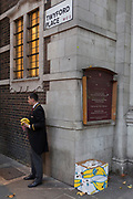A man wearing the uniform of a doorman or hotel clerk, stands on the street to buy bananas, on 22nd November 2017, in London England.