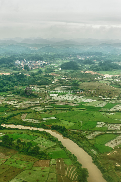 Aerial view of a small village surrounded by farm land and mountains near Guilin, China.