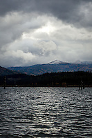 A dusting of snow on the hillsides surrounding Cougar Bay is highlighted by the sunlight breaking through the cloud cover Tuesday.