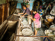 "29 DECEMBER 2018 - BANGKOK, THAILAND: A woman and her husband make longevity noodles in her family shophouse. The family has been making traditional ""mee sua"" noodles, also called ""longevity noodles"" for three generations in their home in central Bangkok. They use a recipe brought to Thailand from China. Longevity noodles are thought to contribute to a long and healthy life and  are served on special occasions, especially Chinese New Year, which is February 4, 2019. These noodles were being made for Chinese New Year.      PHOTO BY JACK KURTZ"