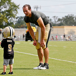 Aug 3, 2013; Metairie, LA, USA; New Orleans Saints quarterback Drew Brees (9) with his two young boys Baylen Brees and Bowen Brees (wearing helmet) following a scrimmage at the team training facility. Mandatory Credit: Derick E. Hingle-USA TODAY Sports