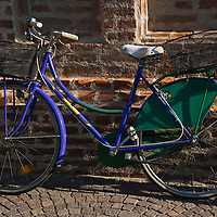 Bicycle parked in front of brick building in the street, Cherasco, Piedmont, Italy