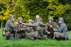 Re-enactors portrayiing panzer grenadiers and fallschirmjäger prepare to take up positions during a battle battle re-enactment on Pickering Showground<br />