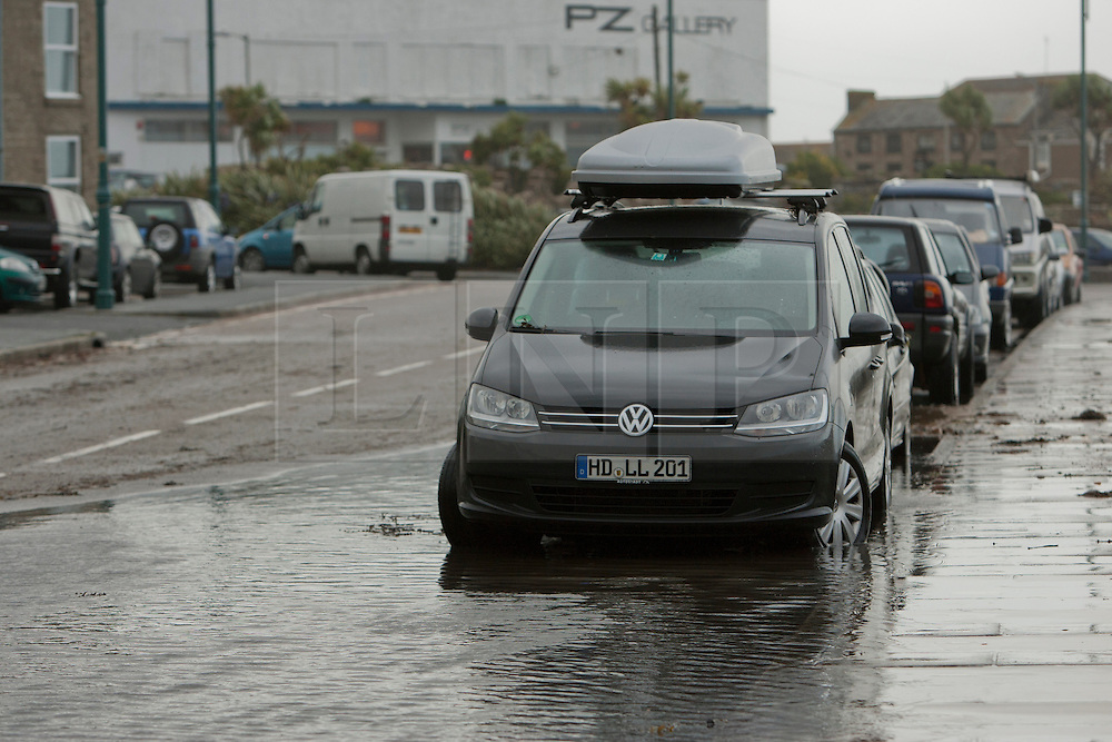 © Licensed to London News Pictures. 15/08/2012. Penzance, UK. A car is parked in a flood caused by sea water deposited on the road by strong winds and large waves along Penzance Promenade. The Police closed the road due to the waves crashing over the road due to high winds but many motorist ignored the warnings Photo credit : Ashley Hugo/LNP. Photo credit : Ashley Hugo/LNP