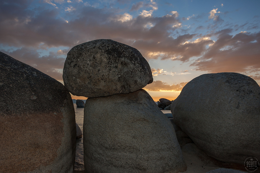 """""""Sunset at Whale Beach, Tahoe 4"""" - Photograph of a sunset at Whale Beach on the East Shore of Lake Tahoe, shot through a pile of boulders. Whale Rock can be seen in the distance."""