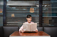 Business woman holding newspaper sitting in cafe portrait