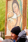 "03 DECEMBER 2011 - PHOENIX, AZ:    A man carries a painting of the Virgin of Guadalupe comforting Pope John Paul II during a procession to honor the Virgin in Phoenix. The Phoenix diocese of the Roman Catholic Church held its Sixth Annual Honor Your Mother Day Saturday to honor the Virgin of Guadalupe. According to Mexican Catholic tradition, on December 9, 1531 Juan Diego, an indigenous peasant, had a vision of a young woman while he was on a hill in the Tepeyac desert, near Mexico City. The woman told him to build a church exactly on the spot where they were standing. He told the local bishop, who asked for some proof. He went back and had the vision again. He told the lady that the bishop wanted proof, and she said ""Bring the roses behind you."" Turning to look, he found a rose bush growing behind him. He cut the roses, placed them in his poncho and returned to the bishop, saying he had brought proof. When he opened his poncho, instead of roses, there was an image of the young lady in the vision. The Virgin is now honored on Dec 12 in Catholic churches throughout Latin America and in Hispanic communitied in the US.   PHOTO BY JACK KURTZ"