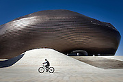 A boy rides a bike near the newly constructed Ordos Museum, which was designed by Chinese architect Ma Yansong. Ma said the structure is said to resemble a Mongolian stone heap.