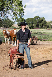 cowboy on a ranch with a saddle