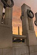 Sunset over the Washington Monument framed by the National World War II Memorial in Washington, DC.