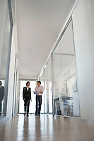 Two businesspeople walking in hallway of office low angle view.