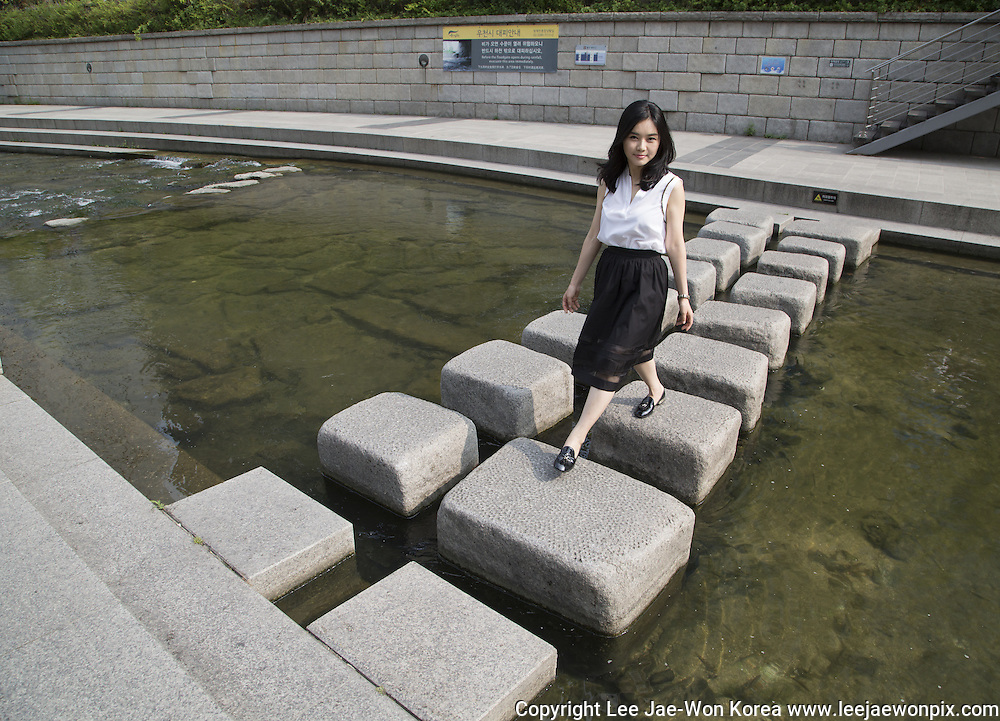 Hyeonseo Lee walks on stepping stones at the Cheonggyecheon stream in central Seoul, June 19, 2015. Lee left North Korea at the age of 17 and came to South Korea in 2008. She is now a human rights campaigner living in South Korea. Photo by Lee Jae-Won (SOUTH KOREA) www.leejaewonpix.com/