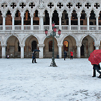 VENICE, ITALY - DECEMBER 17:  Tourists walks in St Mark Square covered with snow on December 17, 2010 in Venice, Italy. Snow has fallen across much of Europe today and is expected to continue over the weekend, causing traffic chaos and disrupting Christmas deliveries. Doge Palace is the former Doge's residence and the seat of Venetian government, the Palace is the very symbol of Venice and a masterpiece of Gothic architecture.