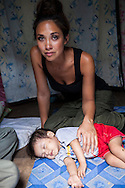 UK celebrity Myleene Klass weeps as she thinks of Vilma Tacuyo's difficulties in their one room home in an urban slum in Paranaque City, Metro Manila, The Philippines on 18 January 2013. Vilma had raised her first 3 children on formula and had to cut down on food for her family to afford it. Both John Ashley, 4, and Justin (sleeping), 3, are malnourished and stunted, and after losing one of her children, she now breastfeeds her youngest, Ulderico. Photo by Suzanne Lee for Save the Children UK