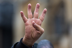 London, UK. 25 January, 2020. A man makes the R4bia hand sign at a protest outside Parliament against the Egyptian government of President Abdel Fattah el-Sisi by supporters of the Egyptian Revolutionary Council and UK anti-Coup organisations.