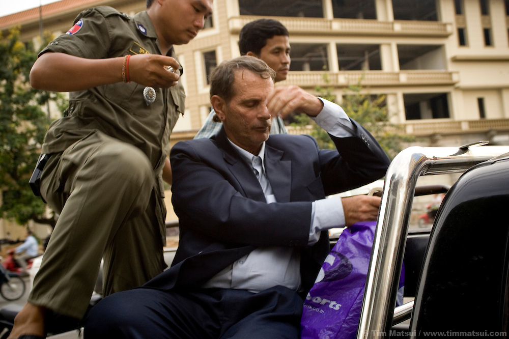 American Thomas Rapanos is handcuffed to a police vehicle following a court appearance in Phnom Penh, Cambodia, where he was charged with debauchery after police burst into his guest house room, finding him with two partially clothed girls aged 12 and 16 years.