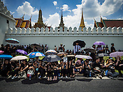 14 OCTOBER 2016 - BANGKOK, THAILAND:  A mourner holds up a portrait of Bhumibol Adulyadej, the King of Thailand, while people wait for the King's body to be brought to the Grand Palace in Bangkok. King Bhumibol Adulyadej died Oct. 13, 2016. He was 88. His death comes after a period of failing health. With the king's death, the world's longest-reigning monarch is Queen Elizabeth II, who ascended to the British throne in 1952. Bhumibol Adulyadej, was born in Cambridge, MA, on 5 December 1927. He was the ninth monarch of Thailand from the Chakri Dynasty and is known as Rama IX. He became King on June 9, 1946 and served as King of Thailand for 70 years, 126 days. He was, at the time of his death, the world's longest-serving head of state and the longest-reigning monarch in Thai history.    PHOTO BY JACK KURTZ