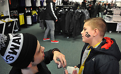 Swansea fans get there face painted prior to kick off. - Photo mandatory by-line: Alex James/JMP - Tel: Mobile: 07966 386802 08/02/2014 - SPORT - FOOTBALL - Swansea - Liberty Stadium - Swansea City v Cardiff City - Barclays Premier League