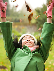 Young girl throwing leaves in the air