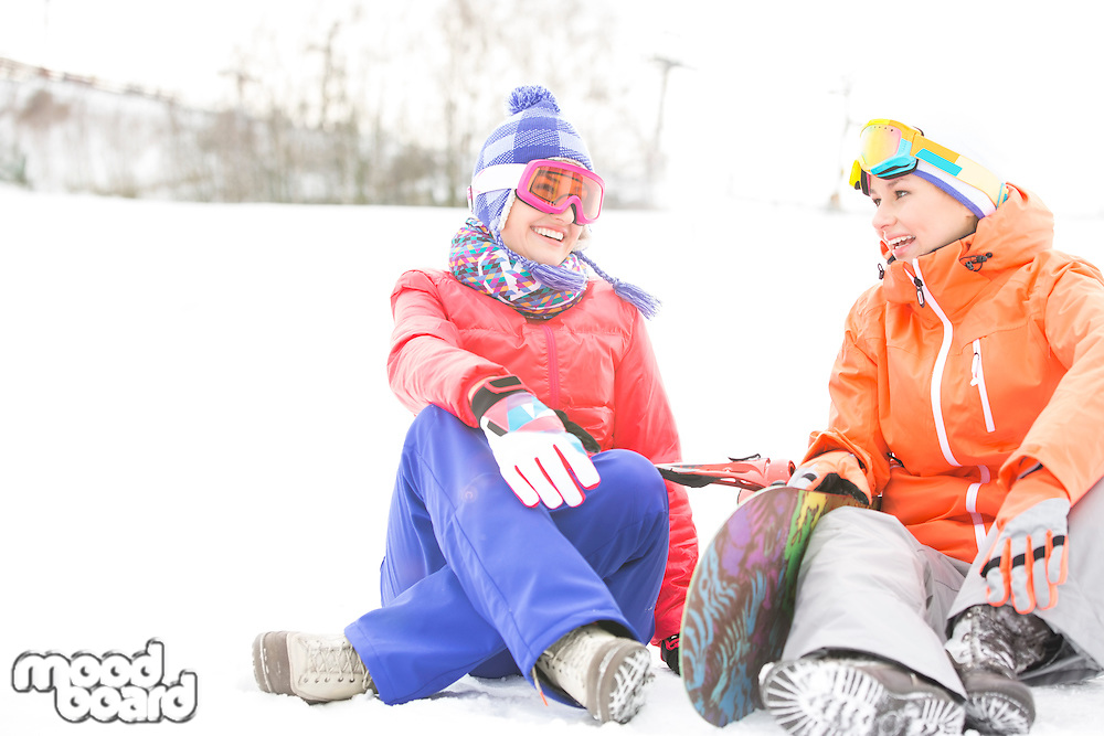 Full length of female friends with snowboard relaxing during winter