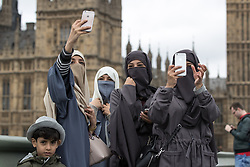 © Licensed to London News Pictures . 29/03/2017 . London , UK . Four women wearing hijabs take selfies from Westminster Bridge outside Parliament in Westminster today (29th March 2017) . Photo credit : Joel Goodman/LNP