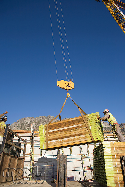 Workmen manoeuvre planks on tower crane