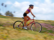 Young woman bicycling through park in San Diego, CA.