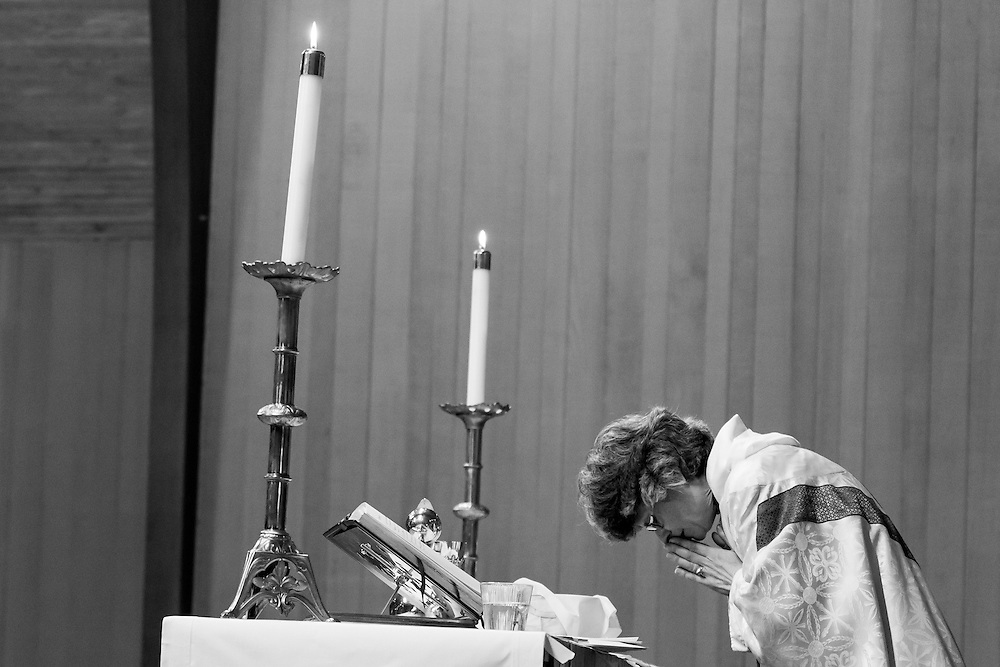 Rev. Sara Fischer prays prior to communion during high mass at St. David of Wales Episcopal Church in Portland, Or.
