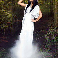 A young oriental woman in traditional Vietnamese hat and flowing white dress, posing in vibrant green fir trees, surrounded by smoke.