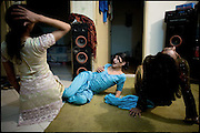 """Chabbo, Kastouri and K. (from the left),  32, 16, 21 years old, transvestites, try a dance, a sort of training in sight of wedding celebration.  Evening in Lahore, Pakistan on Monday, December 01 2008.....""""Not men nor women"""". Just Hijira, Kusra. Painted lips, Kajal surrounding their eyes and colourful veils..Pakistan is today considered a strongly, foundamentalist as well, islamic country. But under its reputation, above all over the talebans' continuos advancing, stirs a completely extraneous world, a multiethnic mixed society. Transvestites make part of it, despite this would not be admitted by a strict law. Third gender, the Hijira are born as men (often ermaphrodites) or with an ambiguous genital situation, and they have their testicles and penis removed through a - often brutal - surgical operation. The peculiarity is that this operation does not contemplate the reconstruction of a female organ. This is the reason why they are not considered as men nor women, just Hijira. They are often discriminated, persecuted  and taxed with being men prostitutes in the muslim areas. The members of this chast perform dances during celebrations, especially during weddings, since it is anciently believed that an EUNUCO's dance and kiss in the wedding day brings good luck to the couple's fertility...To protect the identities of the recorded subjects names and specific .places are fictionals."""
