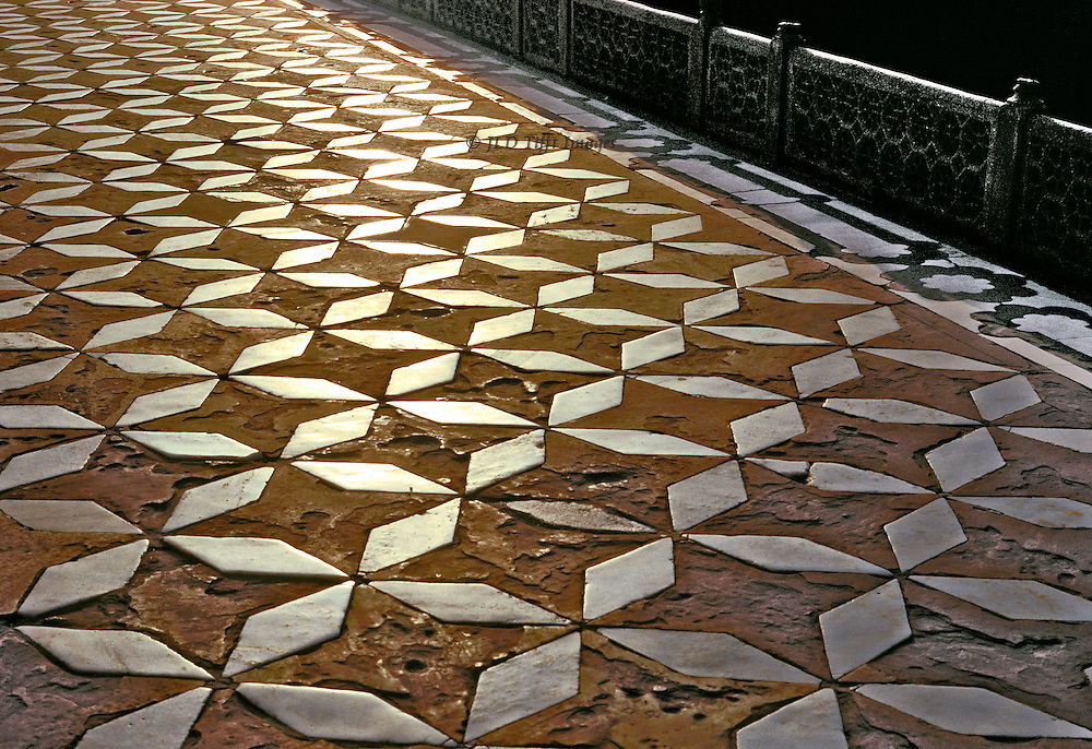 Pavement of the terrace of the Taj Mahal, white marble lozenges set into red sandstone paving tiles.  Early morning sun makes the marble gleam.