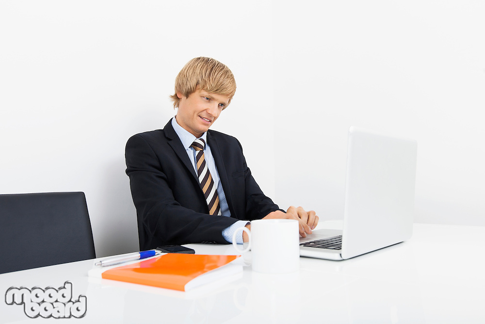 Confident businessman using laptop at desk in laptop