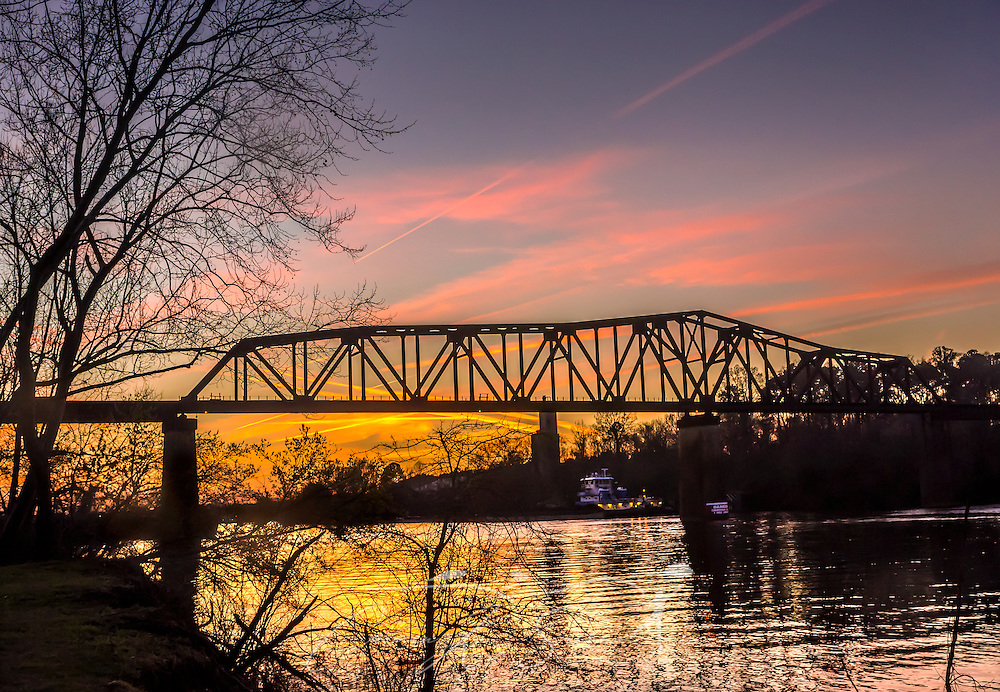 The sun sets on the M&O Railroad trestle, viewed from the Tuscaloosa Riverwalk, March 18, 2014 in Tuscaloosa, Alabama. The wooden and steel truss bridge was build in 1898 for the Mobile and Ohio Railroad. At 135 feet high and 3,600 feet long, it is considered by many to be the country's longest wooden trestle still in use. (Photo by Carmen K. Sisson/Cloudybright)