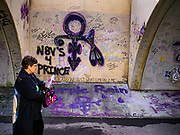 21 APRIL 2017 - CHANHASSEN, MN: A woman walks past graffiti honoring Prince in the pedestrian tunnel in front of Paisley Park, his former home and recording studio. The tunnel has become a memorial to Prince, people have drawn graffiti in the tunnel honoring him and they leave memorials in the tunnel. The superstar died from an accidental overdose of the opioid fentanyl on April 21, 2016. Friday was the first anniversary of his death. Crowds of people gathered at Paisley Park, which is now a museum, to honor the Minnesota born musician.     PHOTO BY JACK KURTZ