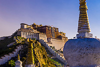 The Potala Palace (a UNESCO World Heritage Site) with stupas in front. The palace was the chief residence of the Dalai Lama until the 14th Dalai Lama fled to Dharamsala, India, during the 1959 Tibetan uprising. The massive palace contains 999 rooms. Lhasa, Tibet, China.