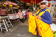 14 OCTOBER 2012 - BANGKOK, THAILAND:  An apron vendor, selling special Vegetarian Festival aprons, looks for customers on the first day of the Vegetarian Festival in Bangkok's Chinatown.  The Vegetarian Festival is celebrated throughout Thailand. It is the Thai version of the The Nine Emperor Gods Festival, a nine-day Taoist celebration beginning on the eve of 9th lunar month of the Chinese calendar. During a period of nine days, those who are participating in the festival dress all in white and abstain from eating meat, poultry, seafood, and dairy products. Vendors and proprietors of restaurants indicate that vegetarian food is for sale at their establishments by putting a yellow flag out with Thai characters for meatless written on it in red.     PHOTO BY JACK KURTZ