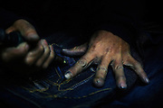 "A worker drills holes in jeans in Mr Huang's factory in Zhongshan city, China..This picture is part of a photo and text story on blue jeans production in China by Justin Jin. .China, the ""factory of the world"", is now also the major producer for blue jeans. To meet production demand, thousands of workers sweat through the night scrubbing, spraying and tearing trousers to create their rugged look. .At dawn, workers bundle the garment off to another factory for packaging and shipping around the world..The workers are among the 200 million migrant labourers criss-crossing China.looking for a better life, at the same time building their country into a.mighty industrial power."