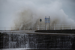 © Licensed to London News Pictures. 21/10/2014. Aberystwyth Wales. At daybreak on Tuesday 21 October 2014, gale force winds and a high tide combine to bring waves crashing into the harbour walls at Aberystwyth, Ceredigion west Wales UK. <br />
