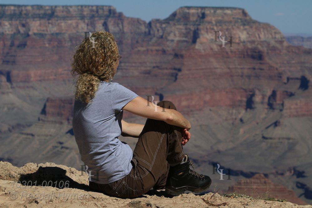 Woman in Asolo hiking boots rests on ledge enjoying sweeping view from Mather Point on South Rim of Grand Canyon National Park, Arizona.