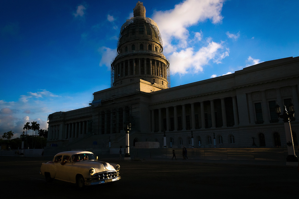 A vintage car passes the National Capitol Building in Old Havana, Cuba.